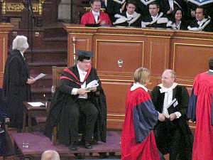 University - Graduation ceremony on Convocation day at the University of Oxford. The Pro-Vice-Chancellor in MA gown and hood, Proctor in official dress and new Doctors of Philosophy in scarlet full dress. Behind them, a bedel, a Doctor and Bachelors of Arts and Medicine graduate.