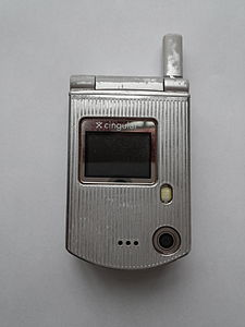 The front of a small, silver flip-phone, shut, taken against a white background.