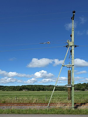 Pole with tension weight for overhead lines.