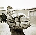 Polish youngster carrying bread made from Red Cross flour at an evacuation camp, Iran, 1943 (35535341954).jpg