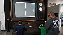 Two children are seen playing a game of Pong on a large-scale monitor.