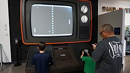 Two children playing Pong on a large-scale monitor.