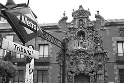 El Museo Municipal, antiguo Real Hospicio del Ave María y San Fernando, visto desde la boca de Metro de Tribunal, en la Calle Fuencarral. La forja del diseño de Antonio Palacios (1919) es una de las formas omnipresentes en el mobiliario urbano madrileño (junto a las farolas «fernandinas»), y convive armónicamente con una de las máximas expresiones del barroco tardío español: la portada del Hospicio, obra de Pedro de Ribera, levantado entre 1722 y 1726, más propia de un palacio aristocrático que de una casa de beneficencia. Llegó a albergar 3.000 asilados y desempeño su función original hasta 1922, cuando a iniciativa de la Real Academia de San Fernando, se le salvó del derribo. Desde entonces funciona como Museo Municipal y es el epicentro de la vida nocturna en el barrio de Malasaña.