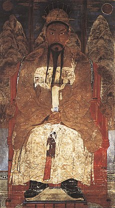 Asian man with mustache and gold robes, sitting down.