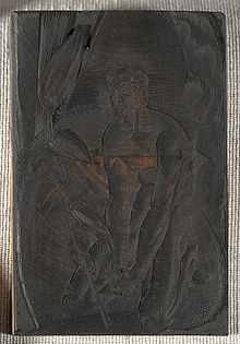 Photograph of an engraved piece of wood, on which is an image of a man kneeling.