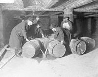 Prohibition agents destroying barrels of alcohol in accordance to the 18th amendment, which made alcoholic beverages illegal throughout the entire decade