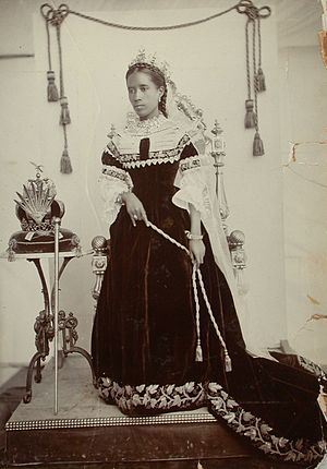 Ranavalona III - The queen standing next to the Royal crown and sceptre