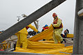 Responders work together to load hundreds of feet of boom onto vessels at the Texas City Dike in Texas City, Texas, March 23, 2014 140323-G-HN254-890.jpg