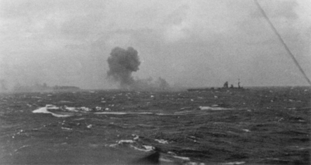 Rodney firing on Bismarck, which can be seen burning in the distance Rodney firing on Bismarck.png