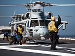 Sailor directs an MH-60S Sea Hawk on USS John C. Stennis' flight deck. (29460669694).jpg