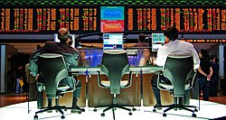 Two traders sit at computer monitors with financial information.