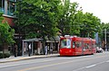 Seattle SLU Streetcar - red car pulling up to a stop (2010).jpg