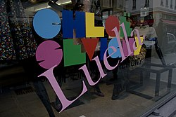 "A storefront window with a large slanted ""Luella"" superimposed over a multi-coloured name logo that reads ""CHLOË SEVIGNY""."