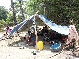 Sri Lankan Civil War - Shelter built from tarp and sticks. Pictured are displaced persons from the civil war in Sri Lanka
