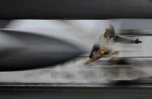 Modern United States Navy carrier air operations - A shooter (also known as a catapult officer) gives the signal to launch an F/A-18.