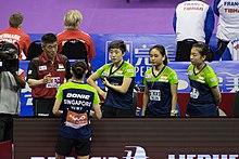 Vier Spieler stehen und hören ihrem Trainer zu.