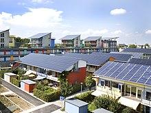Tüm eğimli çatıları güneş panelleriyle kaplı evlerin kısa terasları