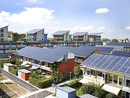 Flere fargerike bygninger med tak helt dekket med solcellepaneler.