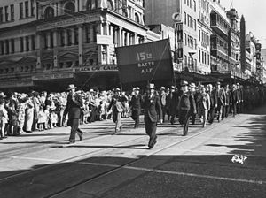 Men in suits and hats march down a city street with a banner