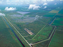 A color photograph taken from the air showing orderly sugarcane fields bordered by canals; to the south are the Everglades in a more natural state; in the center are a series of manmade cement ponds that act as stormwater treatment areas