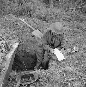 53rd (Welsh) Infantry Division - Fusilier W. Nodder of the Royal Welch Fusiliers writes home from his slit trench before the attack on Evrecy, Normandy, France, 16 July 1944.