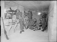 British soldiers man machine guns inside a concrete bunker.