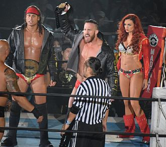 Matt Taven - Taven (left) and Michael Bennett (center) with Maria Kanellis (right) as the IWGP Tag Team Champions in July 2015