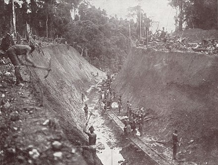 Trenching with hand tools and scant protective gear in rail construction, early 20th century.