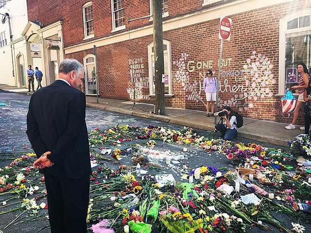 Tim Kaine inspects a makeshift memorial to Heather Heyer