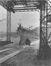 A ship slides out from under a steel framework and into the water.