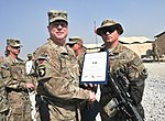 U.S. Army Brig. Gen. Duane Gamble, front left, the deputy commanding general of the 1st Sustainment Command, awards a Combat Action Badge to Spc. Patrick B. Epps, with the 864th Engineer Battalion, assigned to 131007-A-WQ129-008.jpg