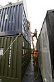 U.S. Sailors with Navy Cargo Handling Battalion 1 prepare a shipping container for offloading from the vehicle cargo ship USNS Pililaau (T-AKR 304) during the Combined Joint Logistics Over the Shore (CJLOTS) 130418-N-LO372-380.jpg