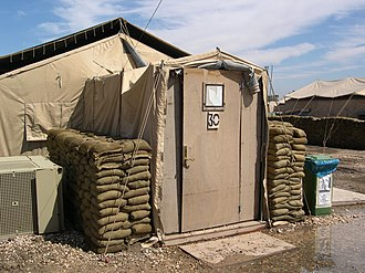 Tent - U.S. Army tent with constructed wooden entrance, air conditioner, and sandbags for protection. Victory Base, Baghdad, Iraq (April 2004).