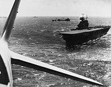 Photographie prise d'un avion dont on voit clairement l'empennage. À droite se trouve un porte-avions d'où l'appareil vient certainement de décoller. Plusieurs navires sont visibles à l'arrière-plan.