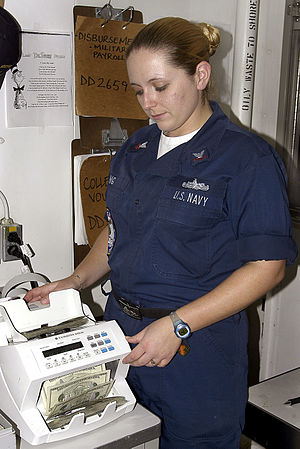Currency-counting machine - A U.S. Navy Disbursing Clerk using a Cummins Allison JetScan to count United States twenty-dollar bills.