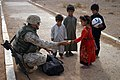 US Navy 041031-M-0036Y-046 Gunnery Sgt. Jimmy Craig of Murfreesboro, Tenn., assigned to 4th Civil Affairs Group, hands a box of crayons to an Iraqi girl in the city of Atkashat, Iraq.jpg