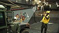 US Navy 051002-N-7945K-050 Boatswain's Mate 3rd Class William Narcusbrown, assigned to a Landing Craft, Utility (LCU) from Assault Craft Unit Two, directs the driver of a High Mobility Multipurpose Wheeled Vehicle.jpg