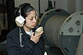 US Navy 070504-2970B-N-002 Seaman Olga Dominguez listens to the other end of a sound-powered phone as she waits for a command to start the mooring process during a fast cruise aboard Nimitz-Class aircraft carrier USS Carl Vinso.jpg