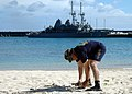 US Navy 070625-N-3019M-001 Chief Electrician's Mate Noel Corneja, assigned to the Sasebo-based mine warfare ship USS Patriot (MCM 7), picks up trash on Nanta Beach during a two-day port visit to the island.jpg