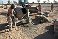 US Navy 071107-M-4804L-021 A Seabee assigned to Naval Mobile Construction Battalion (NMCB) 15, mixes setting concrete while building structures for the different units in the Al Anbar province of Iraq.jpg