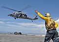 US Navy 101009-N-3620B-037 Aviation Boatswain's Mate (Fuel) Airman Adam M. Pond signals to an MH-60S Sea Hawk helicopter to take off after dropping.jpg