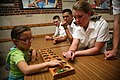 US Navy 110906-N-YM440-123 Midshipman 3rd Class Alyssa Wolken, a Navy ROTC member at the University of Nebraska, plays with a student at Everett El.jpg