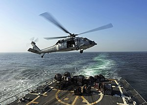 US Navy 111213-N-VH839-027 A helicopter turns away from the flight deck after lowering pallets of food.jpg