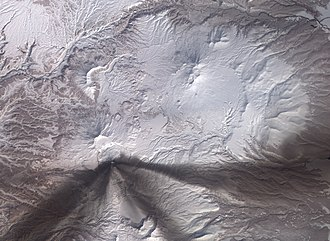 Karymsky (volcano) - Satellite image of the area around the volcano. Ash from earlier eruptions has settled onto the snowy landscape, leaving dark grey swaths. The ash stains are confined to the south of the volcano's summit, one large stain fanning out toward the south-west, and another toward the east.