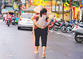 Walking mother with her little daugher on her back Vietnam.jpg