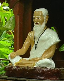 Thai image of Jīvaka, in a white robe and bearded, wearing prayer beads around his neck
