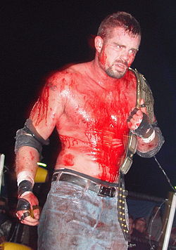 Adult white male covered in blood wearing blue jeans and wrestling gear while holding a gold championship wrestling belt.