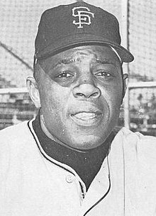 Portrait shot of an older Willie Mays in a San Francisco Giants uniform, the top button of which is undone