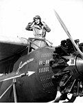 Woman in a cheetah print coat, aviator helmet and goggles, standing in the cockpit of pontoon plane, probably Washington State (4951754034).jpg