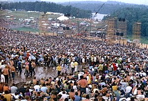 English: The crowd at Woodstock fills a natura...